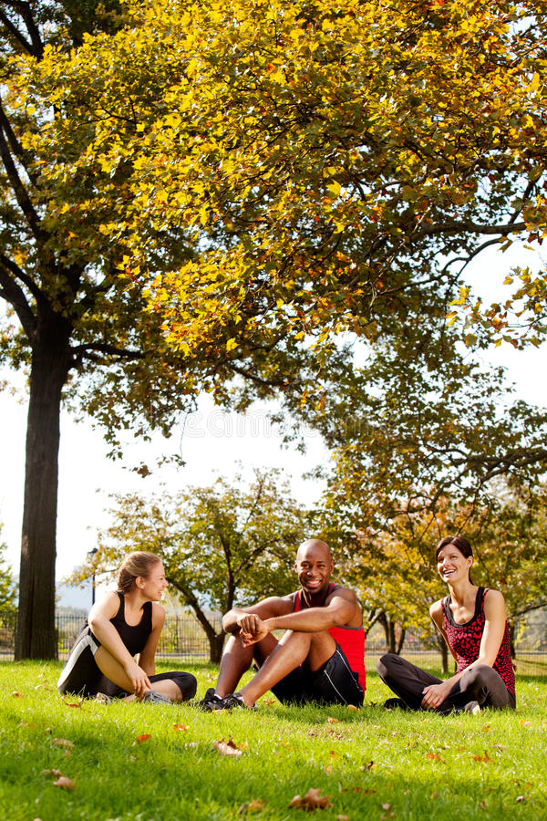 Relax Park Summer. A group of people relaxing in the park after exercise stock photography