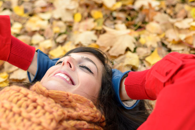 Relax and peace on happy autumn. Happy woman on autumn season relax. Brunette girl lying down and smiling on fall golden leaves in park. Tranquility and peace royalty free stock photography