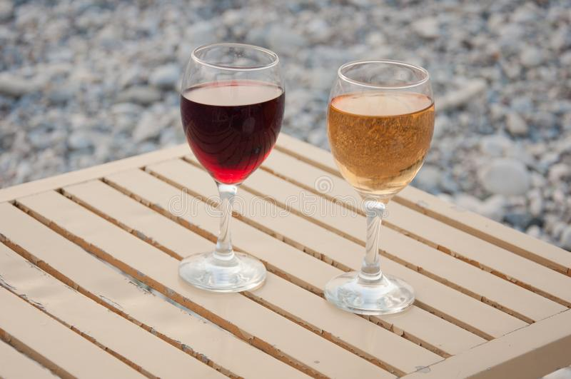 Relax on pebble beach. Two wineglass stand on table in afternoon. Relax on pebble beach. Two wineglass with red, white wine stand on table in afternoon royalty free stock photos