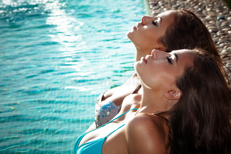 Relax by the pool. Two young women relax and take sunbath in swimmingpool royalty free stock images