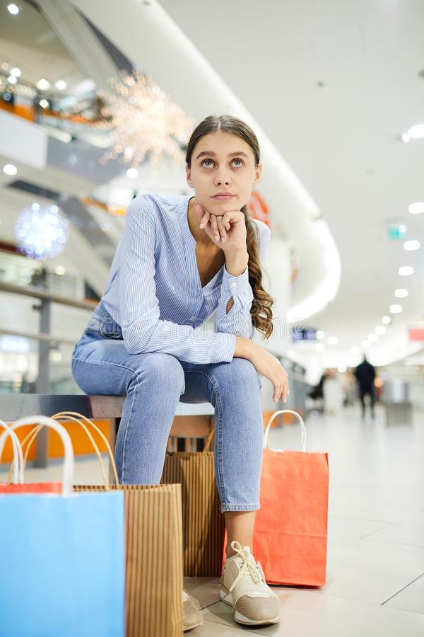 Relax after shopping. Pensive or tired shopper in casualwear sitting in large mall after shopping and having rest stock images