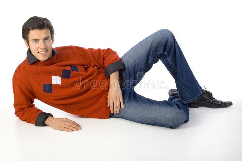 Relax, takie it easy... Smiling, handsome man wearing orange jersey, black shirt and denim jeans. Lying, looking at camera. Isolated on white in studio royalty free stock images