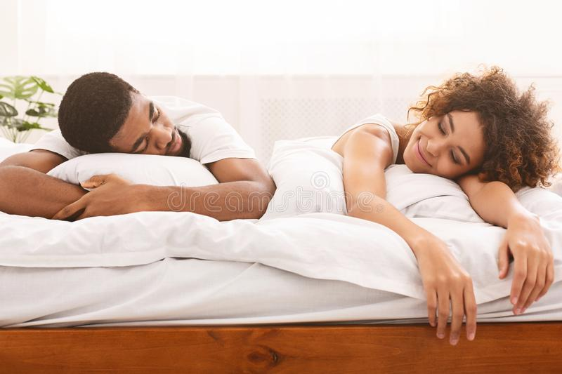 Happily tired african lover resting on bed together royalty free stock photos
