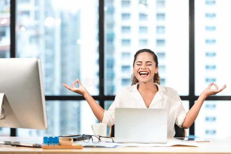 Relax time.  Successful smilling business woman relaxing and  meditating after working in modern office, mindful peaceful and prac royalty free stock photography