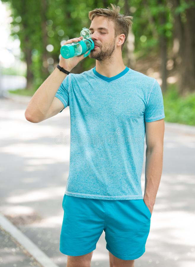 Relax time. time to relax. relax time of healthy sportsman. athletic man has relax time in forest and drink water. royalty free stock image