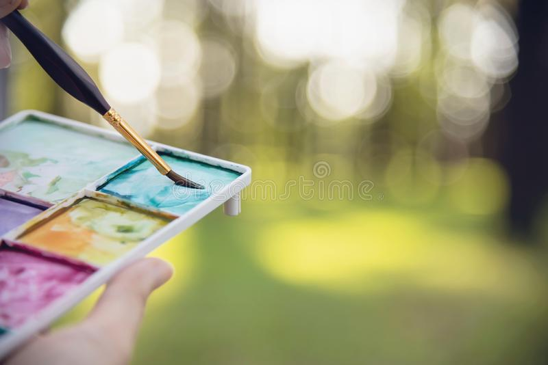 Relax woman painting water colour art work in green garden forest nature. People with creative art in nature stress reduction and meditation concept stock photography