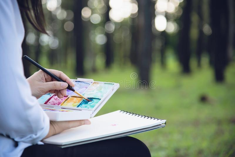 Relax woman painting water colour art work in green garden forest nature. People with creative art in nature stress reduction and meditation concept royalty free stock photo