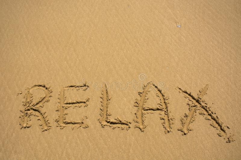 Relax word on sand beach texture. Natural sand background for design. Summer concept stock photos