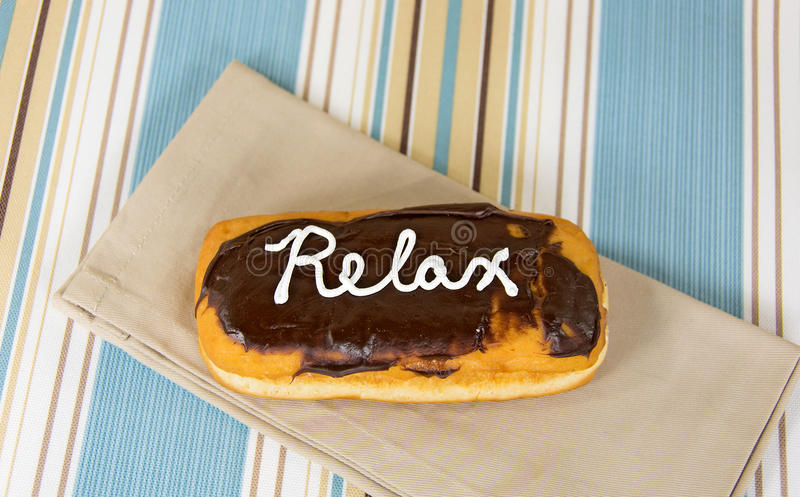 Relax written on chocolate donut. Word relax in white icing on chocolate long john donut royalty free stock photo