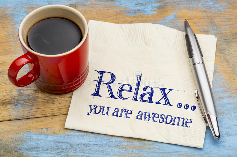 Relax, you are awesome. Reminder or positive affirmation - handwriting on a napkin with cup of coffee stock image