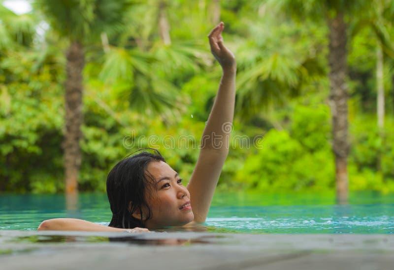 Relaxamento chinês asiático atrativo e bonito novo da mulher feliz na natação tropical da estância de verão na associação da infi imagens de stock