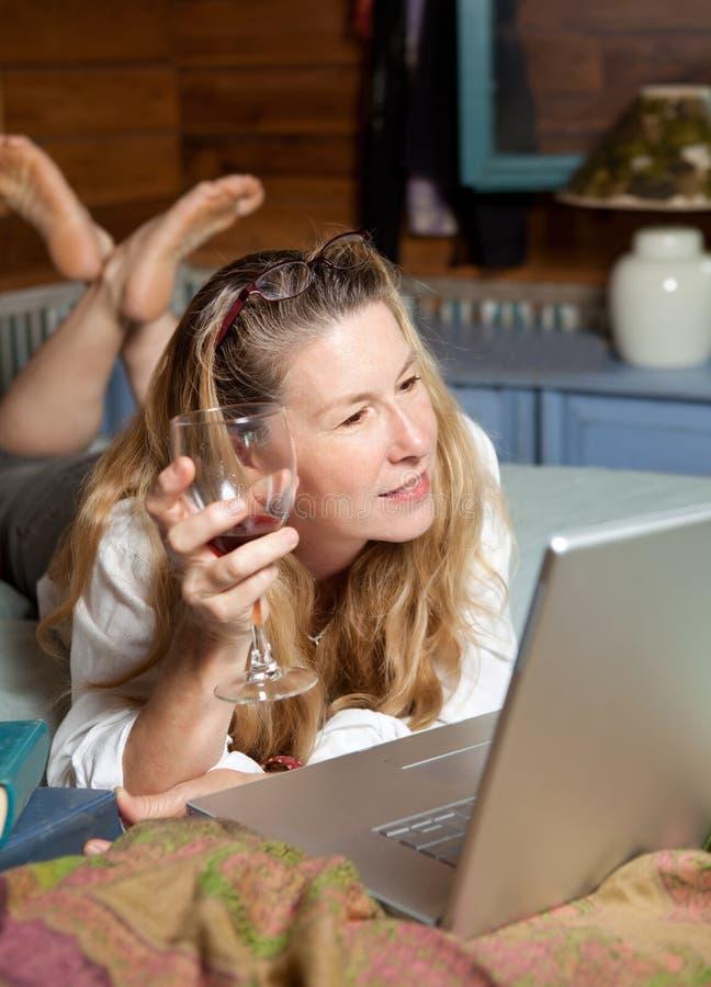 Relaxamento com vidro do vinho no computador portátil foto de stock