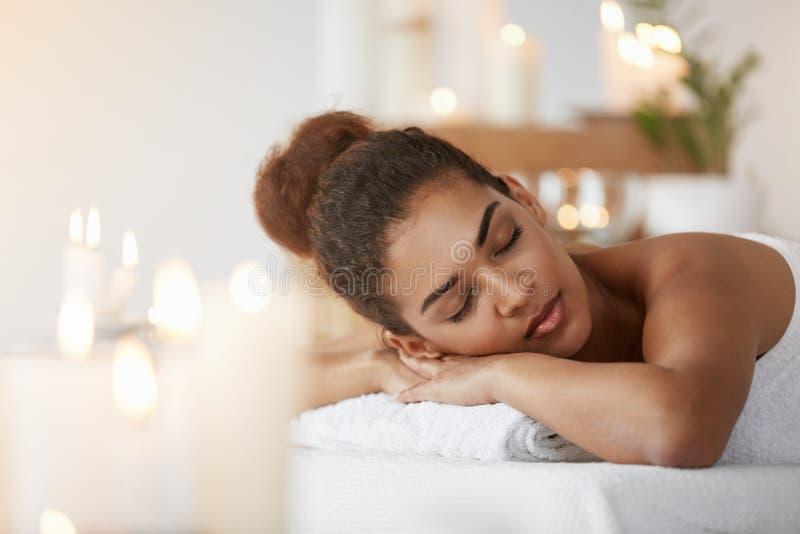 Relaxamento de descanso da menina africana macia com os olhos fechados no salão de beleza dos termas fotos de stock