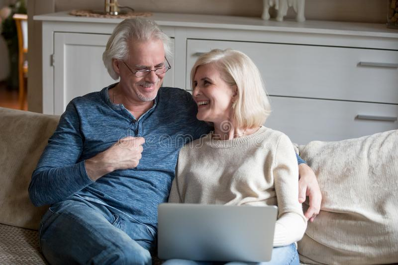 Relaxamento de riso dos pares superiores felizes com o portátil na sala de visitas fotografia de stock royalty free