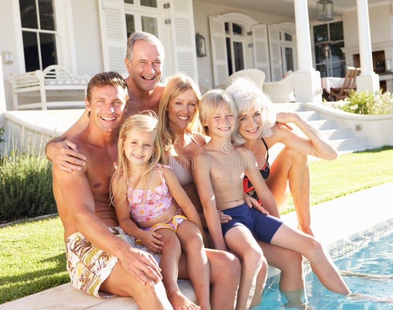 Relaxamento exterior da família extensa pela piscina