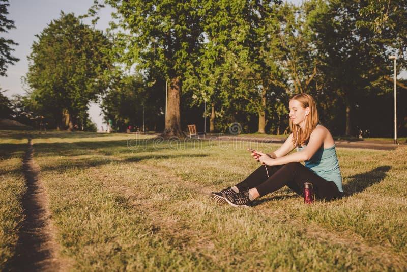 Relaxamento exterior Jovem mulher que senta-se no parque, relaxando após ter corrido e ter usado seu smartphone foto de stock