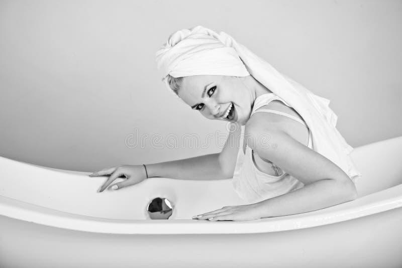 Relaxamento fêmea em uns termas mulher na toalha que senta-se na banheira e no sorriso imagem de stock