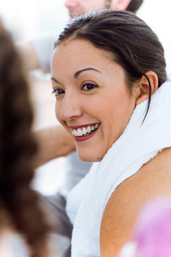 Relaxamento fêmea novo na esteira da ioga e fala após sess do exercício imagem de stock royalty free