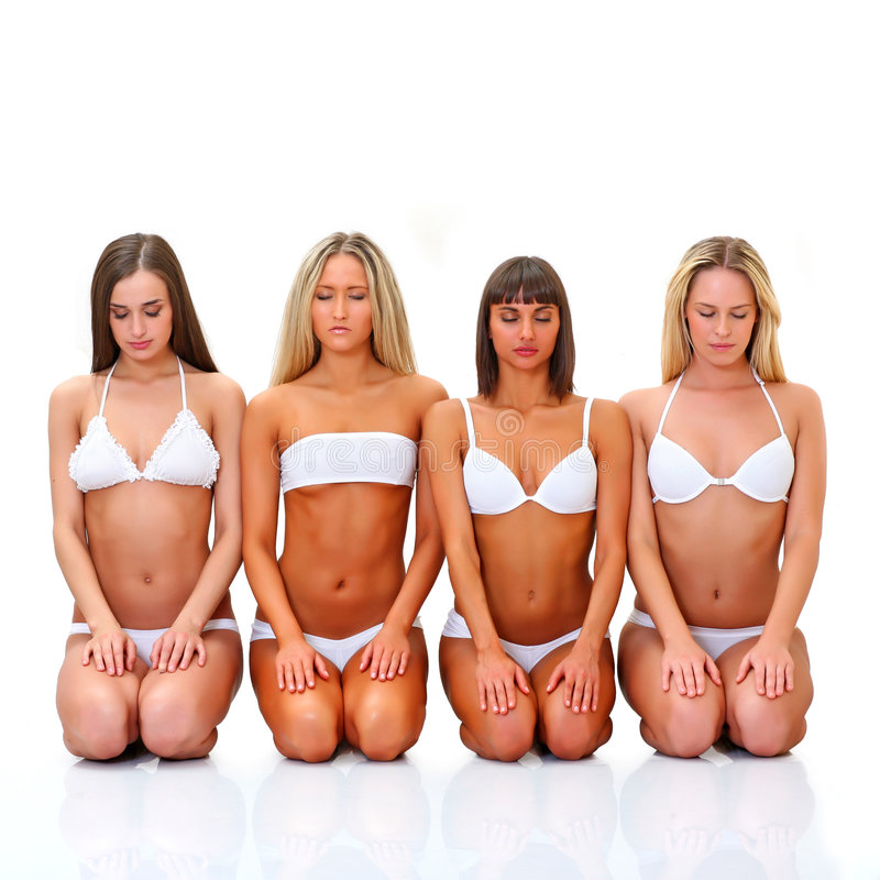 Relaxation. Four beautiful young women in white underwear sit in a lap blindly royalty free stock photos