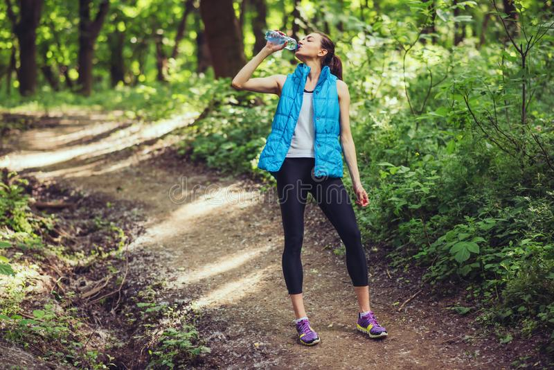 relaxation après séance d'entraînement dure Jeune belle femme courante sur la nature, forêt, eau potable de backgorund de parc images stock