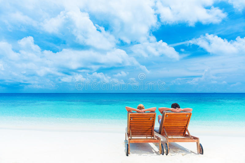 Relaxation on the beach. Two happy people relaxing on the beach, sitting down on comfortable sunbed and taking sunbath, rear view, summer holidays concept royalty free stock photography