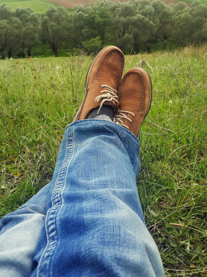 Relaxation concept, man legs on grass during sunny serene stock photography