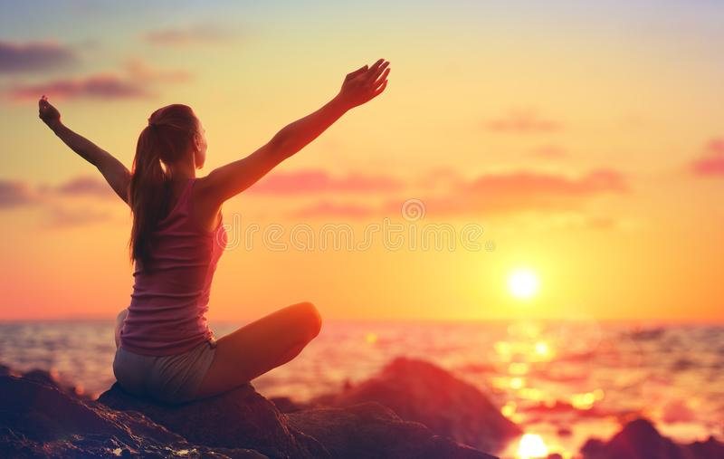 Relaxation et yoga au coucher du soleil - fille avec les bras ouverts photos libres de droits