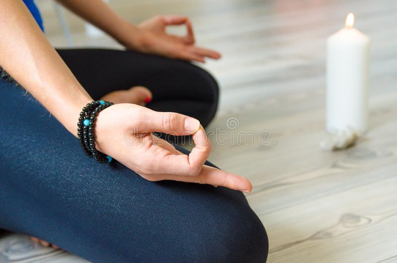Relaxation, exercise, hands, yoga. Proper Breathing. Relaxation, exercise, hands, yoga. The woman has a bracelet, feathers, folded arms on her hand, candle royalty free stock photos