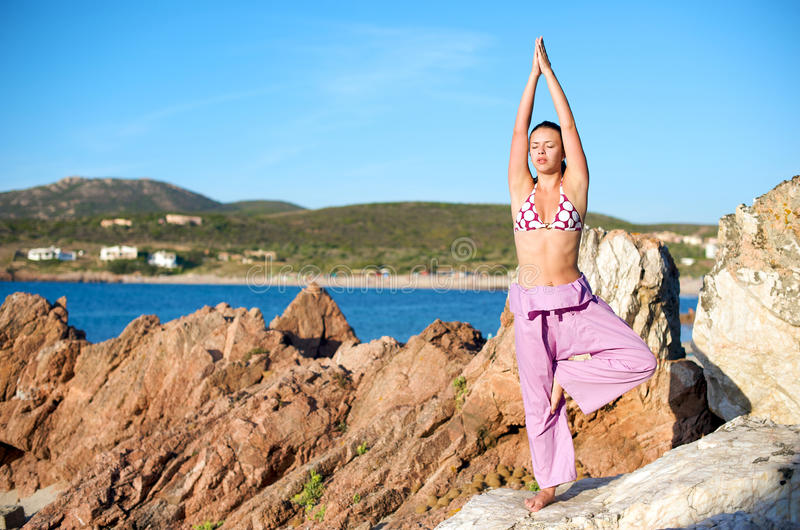 Relaxation exercises with sea view. Pretty woman doing relaxation exercices with a sea view at sunset time in Sardinia, Italy stock image