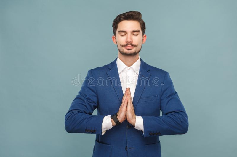 Relaxation and harmony. Man meditating after work. Business people concept, richly and success. Indoor, studio shot on light blue background stock image