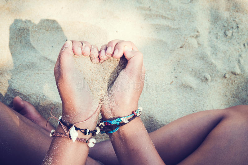 Relaxation and Leisure in Summer lifestyle image of slim tanned girl on beach,. Holding a sand heart symbol in hand. On hands many seashell bracelets. Tropical royalty free stock photography