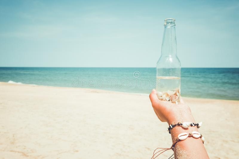 Woman hand holding bottle with seashell at tropical beach in summer stock photos