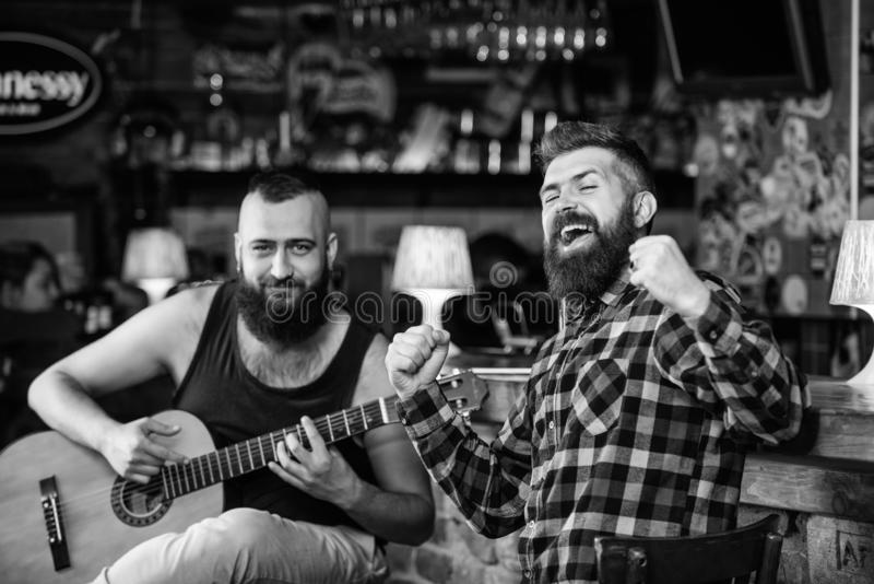 Relaxation in pub. Friends relaxing in pub. Live music concert. Man play guitar in pub. Acoustic performance in pub.  royalty free stock image