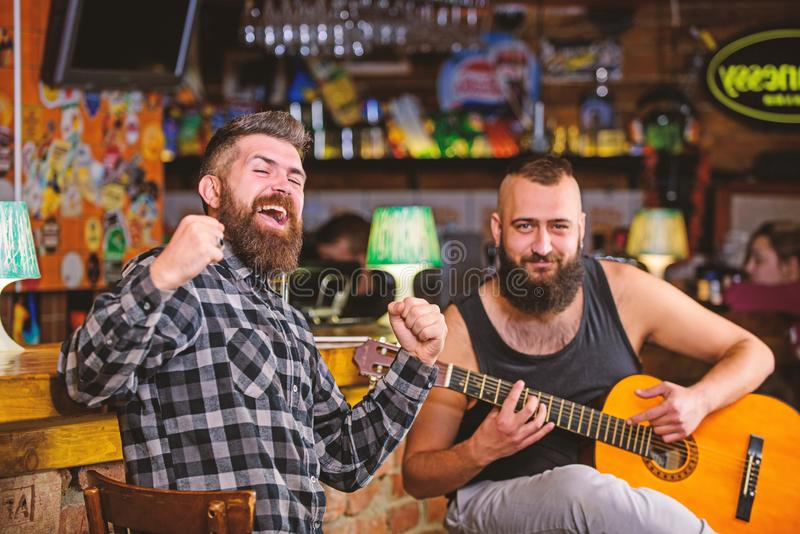 Relaxation in pub. Friends relaxing in pub. Live music concert. Man play guitar in pub. Acoustic performance in pub. Relaxation in pub. Friends relaxing in pub royalty free stock images