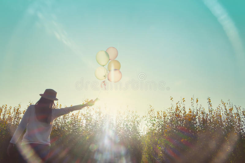 Relaxation and travel outdoor background idea concept. Girl running on the field of yellow flowerwith balloons at sunset. Happy woman on nature, concept about stock photography