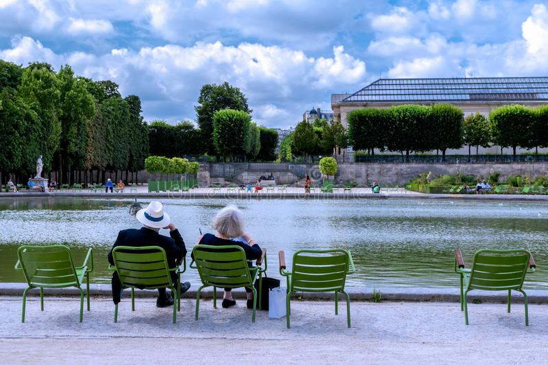 Relaxation at the Tuileries Garden in Paris. An adult couple enjoy a moment of calm in front of the large basin of the Tuileries Garden in Paris, France stock images
