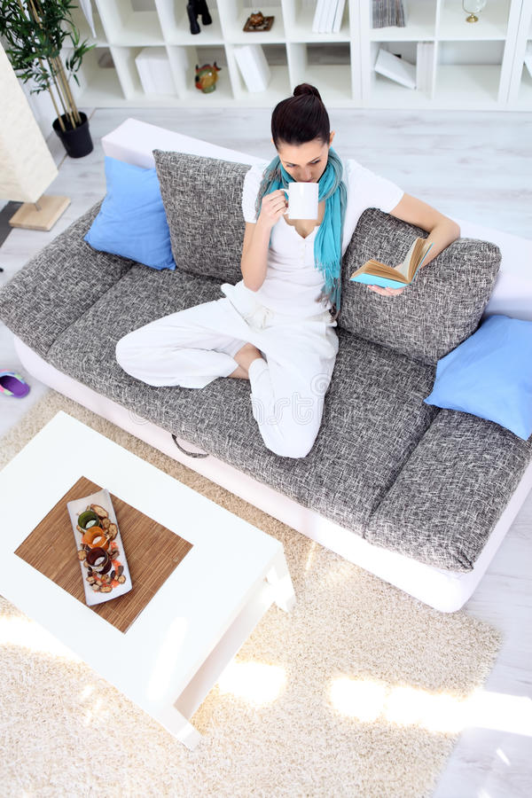 Relaxation woman with tea and book in living room royalty free stock image