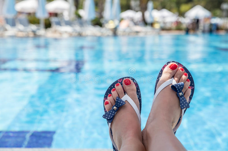 Relaxation. Woman wearing flip-flops laying on the sunbed near the pool royalty free stock photos