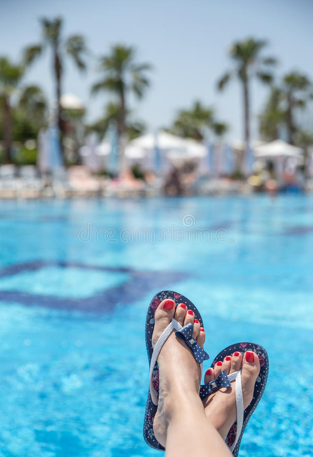 Relaxation. Woman wearing flip-flops laying on the sunbed near the pool stock image