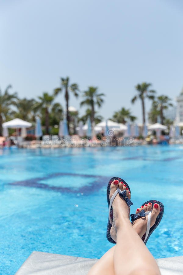 Relaxation. Woman wearing flip-flops laying on the sunbed near the pool stock photography