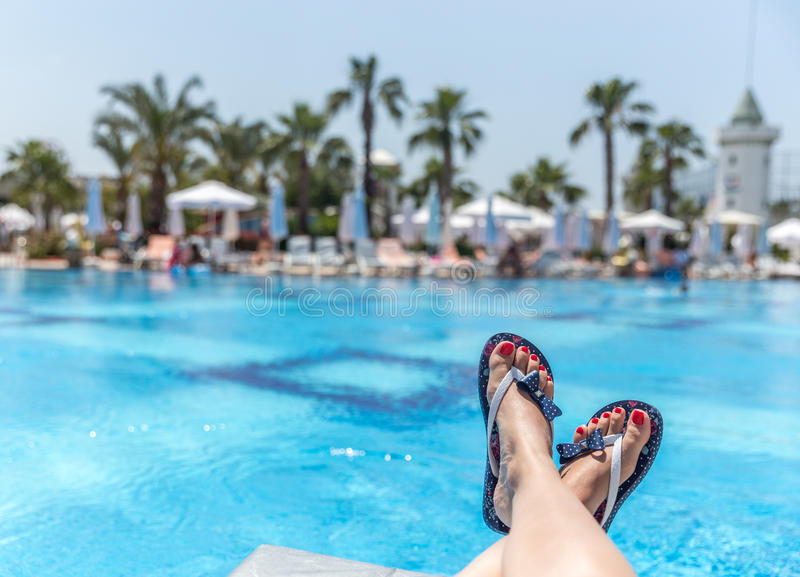 Relaxation. Woman wearing flip-flops laying on the sunbed near the pool royalty free stock photo