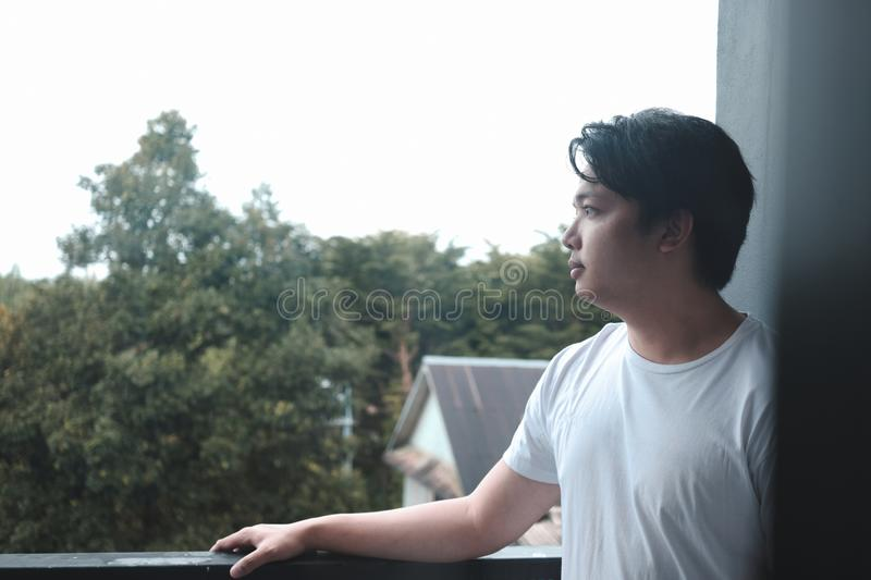 Relaxation of young man looking at view with nice weather and nature background. Close up relaxation of young man looking at view with nice weather and tranquil stock images