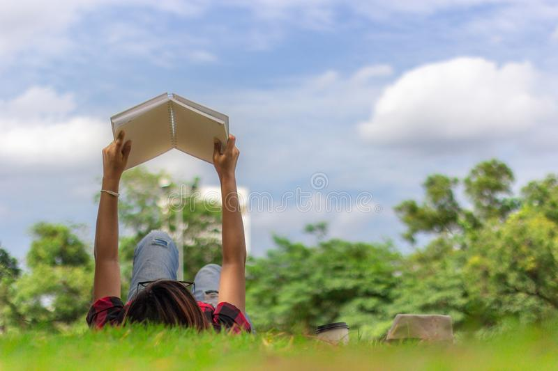 Relaxation of young woman lying on grass field for reading a boo stock image