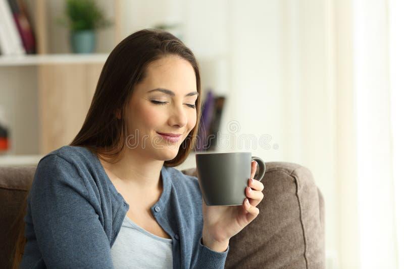 Relaxd-Frau, die einen Tasse Kaffee auf einer Couch genießt lizenzfreie stockfotos
