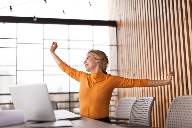 Relaxe do escritório, mulher esticada no local de trabalho fotografia de stock royalty free