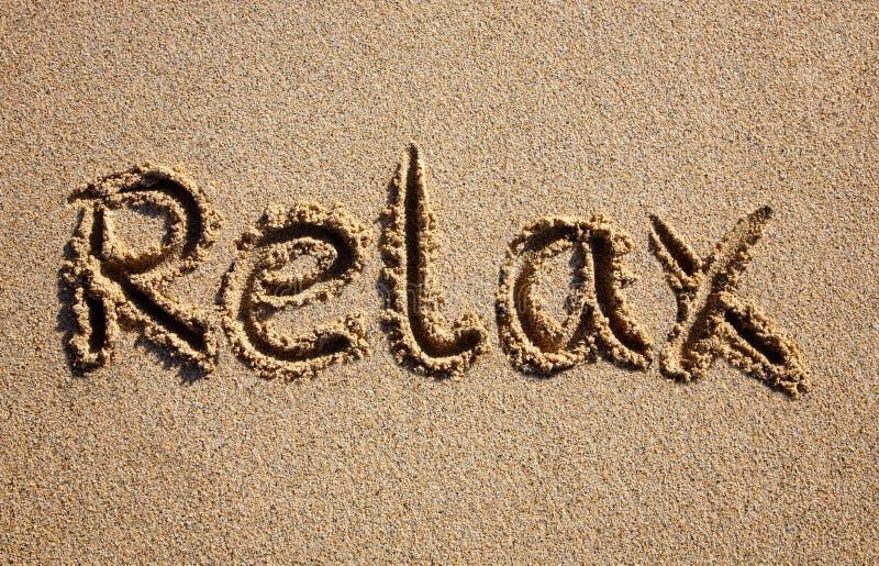 Relaxe, escrito em uma praia. imagem de stock royalty free