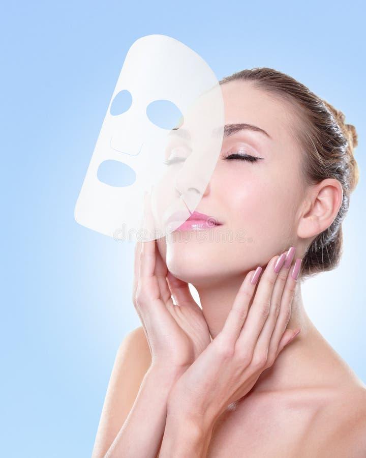 Relaxe a jovem mulher com máscara do facial de pano foto de stock