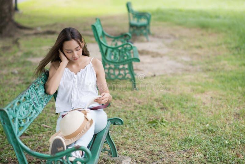 Relaxe a mulher leem o livro no parque foto de stock
