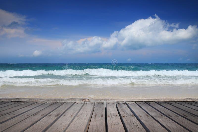 Relaxe o assoalho de madeira do tempo e o fundo bonito do mar fotografia de stock