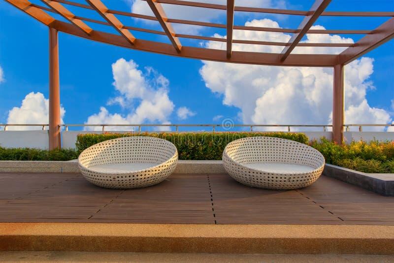 Relaxe o canto no jardim do telhado do condomínio com as cadeiras no fundo do céu azul imagem de stock